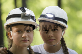 Portrait of cute teen sisters speleologists in helmets in summer