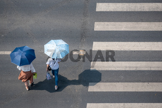 Two women crossing the road outside the pedestrian crossing