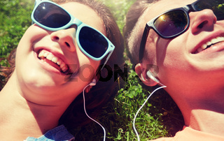 happy teenage couple with earphones lying on grass