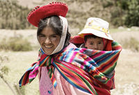 Smiling Quechua Woman Dressed In Colourful Traditional Handmade Outfit And Carrying Her Baby In A Sling. October 21, 2012 - Patachancha, Cuzco, Peru