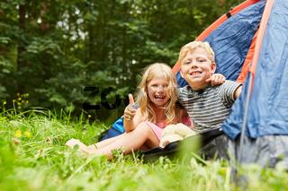 Kinder mit Daumen hoch im Zelt beim Camping