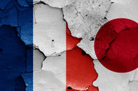 flags of France and Japan painted on cracked wall