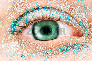 Macro green female eye with glitter eyeshadow, colorful sparks, crystals. Beauty background, fashion glamour makeup concept. Holiday evening make-up detail.