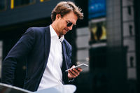 A Handsome And Attractive Office Worker In Sunglasses Is Looking At His Mobile Phone While Standing In The Street
