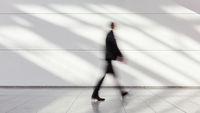 Anonymer Geschäftsmann geht Gang im Büro