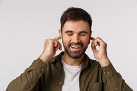Cheerful and carefree, happy good-looking bearded male in coat, close eyes and smiling delighted, touching wireless earphones plugged in ears as enjoying nice sound quality, listen favorite music