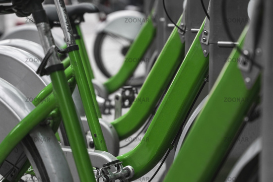 Street transportation green hybrid rent bicycles with electronic form of payment for traveling around the city stand in row on rental network parking lot waiting for cyclists to make bike trip.