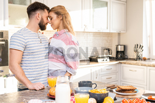 Romantic Couple Embracing in Kitchen