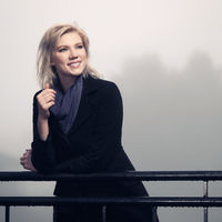 Young fashion woman in black coat leaning on railing in a fog outdoor
