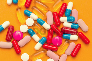 Assorted pharmaceutical medicine pills, tablets and capsules and bottle on orange background. Copy space for text