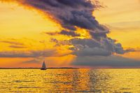 Sonnenuntergang mit Segelboot - a beautiful sunset by the sea with a sailboat and dramatic clouds