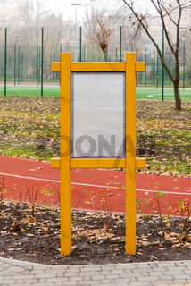 Blank white information board in the park in autumn. Naked trees and autumn leaves on the ground