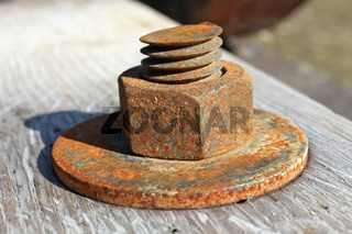 Large rusty nut holds wood  aged planks together background