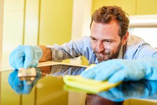 Mann als Hausmann beim Kochfeld reinigen