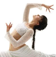 Young gymnast sitting in graceful split in studio