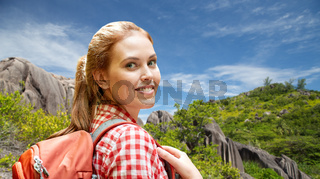 happy woman with backpack over seychelles island