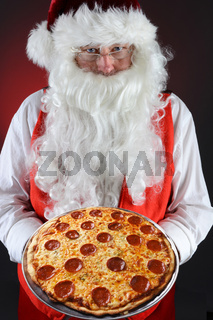 Santa Claus serving a fresh homemade pepperoni pizza. He is holding the platter in both hands in front of his torso.