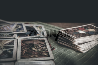 Occult mystic tarot deck and old tarot cards laying on table for a magical pagan ritual psychic destiny reading - Concept of supernatural, witchcraft, destiny and mystical fortune-telling