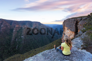 Woman with wind swept hair sitting  on edge of cliffs