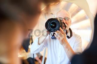 Erfahrener Fotograf mit Kamera macht Porträtfotos