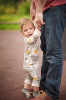 Adorable baby hold hands and try to stand with help of his father