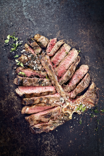 Barbecue dry aged wagyu porterhouse steak sliced and decorated with spice and herbs as top view on an old rusty board with copy space