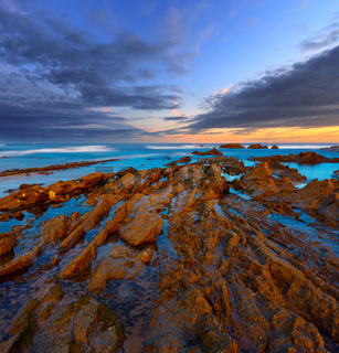 Twilight ocean coast with ribbed stratiform rock