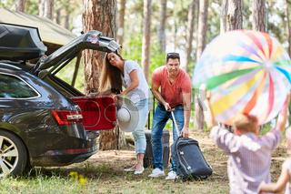 Eltern packen Gepäck in den Kofferraum