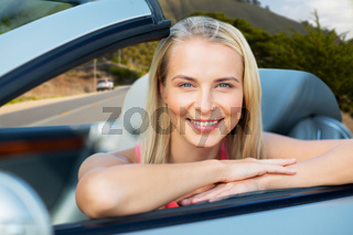 happy woman in convertible car over big sur hills