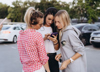 Three beautiful young women are looking at a smartphone