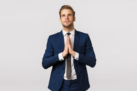 Hopeful attractive blond caucasian guy, male entrepreneur in classic suit, business formal wear, hold hands together in pray, look up sky like believer, praying, making wish, white background