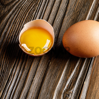 Broken egg with yolk and fresh brown organic eggs on wooden table