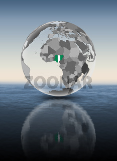 Nigeria on translucent globe above water