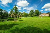 Beautiful park in spring with little castle on green hill in front of blue sky with white clouds