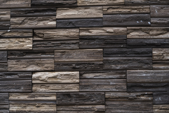 Natural stone bricks as a decoration on a wall. Natural stone wall texture. The walls are made of stones or marbles. Decoration for the walls or febces.