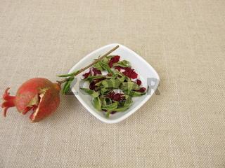 Ein kleiner Granatapfel, getrocknete Granatapfelblätter und Granatapfelblüten in einer Schale