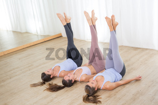 Group of three young sporty attractive women in yoga studio, lying on the floor holdings legs up against white background. Healthy active lifestyle, working out indoors in gym.