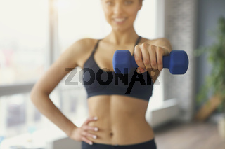 Young sportswoman doing fitness exercises at sport gym