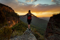 Hiker standing firm on narrow ledge  in wilderness mountains