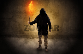 Wayfarer with burning torch in front of crumbly wall concept