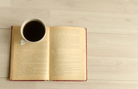 a cup of coffee and an open book on white wooden background.Top view,space for text.