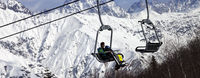 Skiers on ski-lift and snow mountains at winter sun day