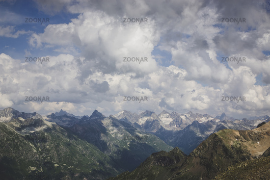 Mountains scene with dramatic cloudy sky in national park of Dombay