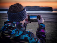Anonymous unrecognizable traveler shooting sunset on seashore