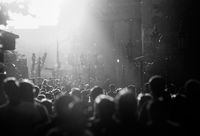 Black and white silhouette of people crowd walking down the pedestrian street under the sunshine