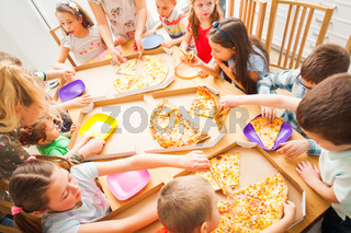 Happy kids eating pizza and having fun together.