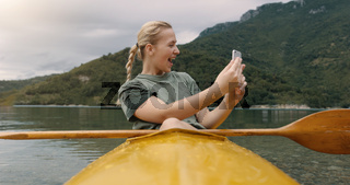 Beautiful young adult woman taking selfie while she is on kayak and having some recreational time on her vacation