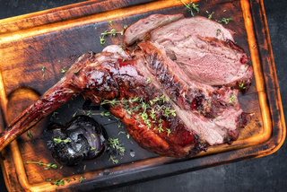 Marinated sliced barbecue aged leg of venison with onion as top view on rustic burnt cutting board