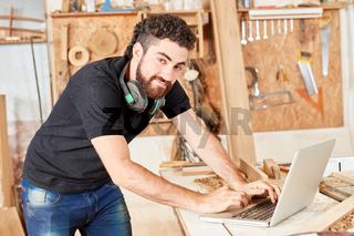 Handwerker schreibt Email auf dem Laptop