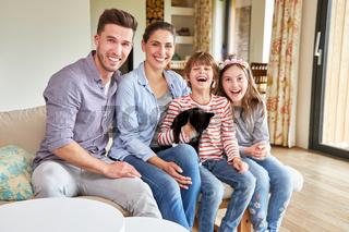 Eltern und Kinder mit Katze im Wohnzimmer